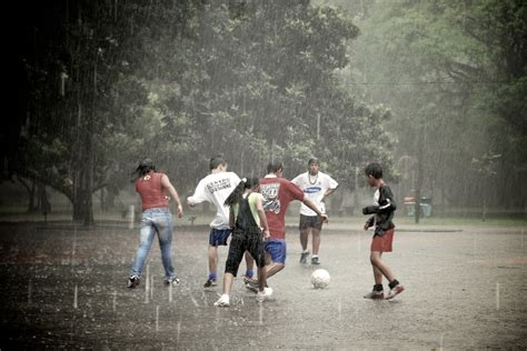 Teenagers playing soccer in the rain | Parque do